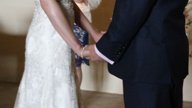 Unidentified couple holding hands at wedding