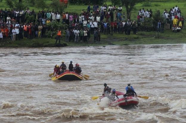Rescue workers search the flooded River Savitri after an old bridge collapsed in Mahad, western Maharashtra state, India, Wednesday, Aug. 3, 2016.