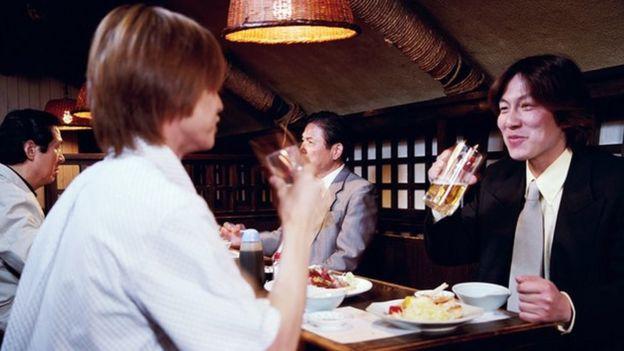 Trabajadores japoneses comiendo y bebiendo en un restaurant
