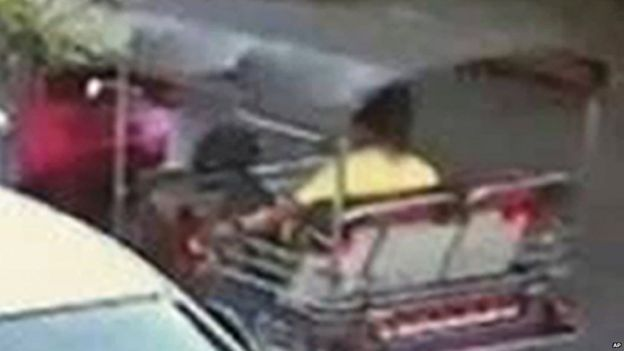 An image released by Thai police of a suspect wearing a yellow T-shirt sitting in a tuk-tuk near the Erewan Shrine