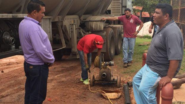 Unos empleados llenar de gasolina los surtidores de la bomba