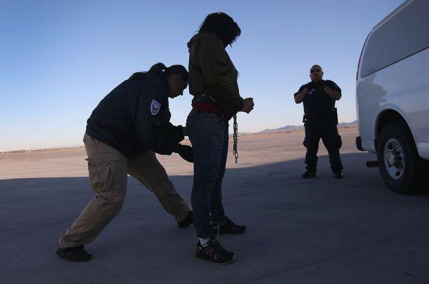 Una agente de seguridad revisa a una Inmigrante indocumentada a punto de ser deportada a Honduras.
