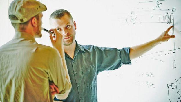 Una persona dándole instrucciones a otra sobre un dibujo en una pizarra