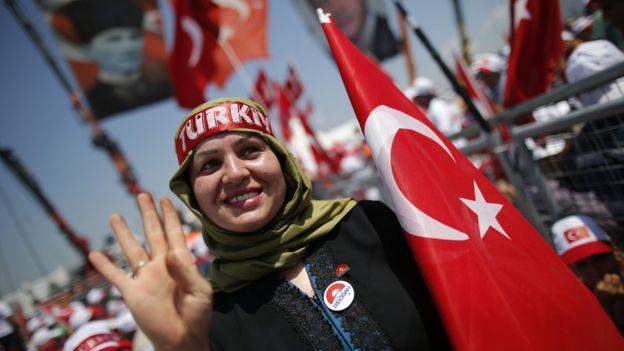 Bir kadın gösterici Rabia işareti yaparken görülüyor.