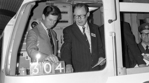 London Transport official showing the Prince Charles, Prince of Wales, the controls in the driver's cab of a Jubilee Line train