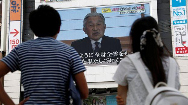 Japoneses en la calle observan el mensaje del emperador en una pantalla gigante