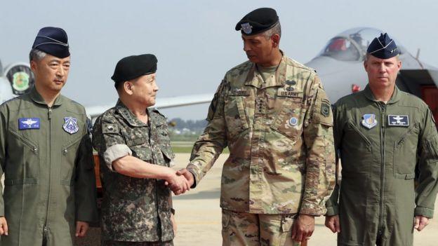 El más alto comandante de EE.UU. en Corea, el general Vincent Brooks (segundo desde la derecha) saluda al presidente del Estado Mayor Conjunto de Corea del Sur, general Lee Sun Jin (segundo desde la izquierda).