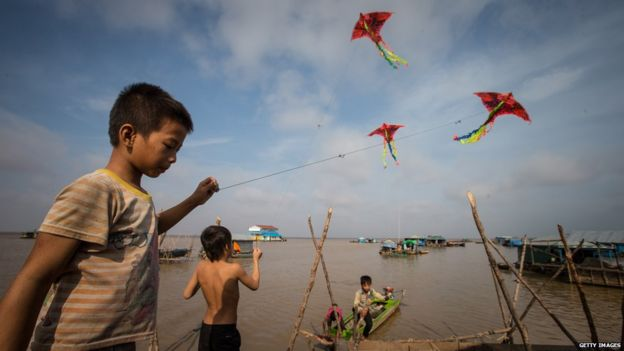 Children play with kites on the floating village on May 13, 2015 on Tonle Sap Lake, Cambodia
