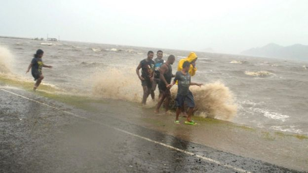 Fijians walk near the coast during a cyclone