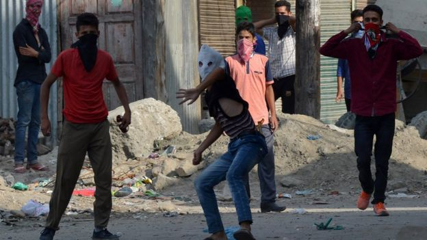 Kashmiri protesters through stones towards Indian government forces.