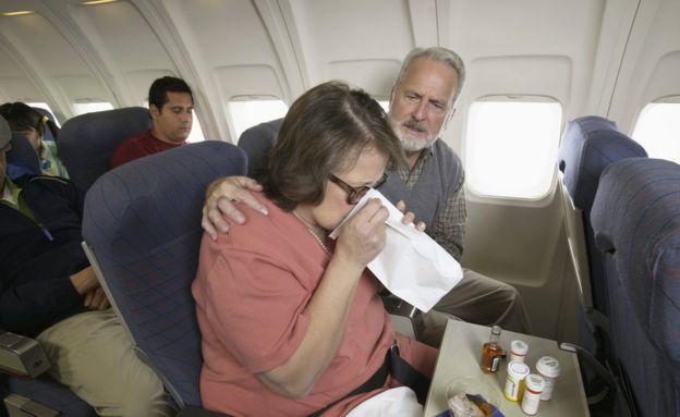 Mujer mareada en un avión con medicamentos y un vaso de licor.