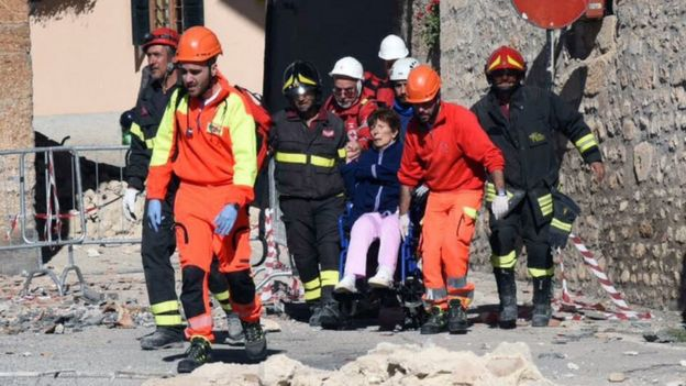 A woman on a wheelchair is carried away by rescuers in Norcia, central Italy