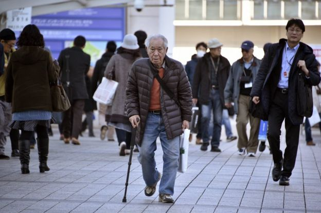 An elderly man walks with a stick