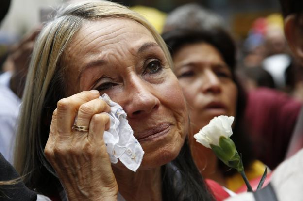 A woman cries as she watches a live broadcast from Havana of the ceremony of the agreement between the Colombian president and the head of the Farc rebels on a cease-fire and rebel disarmament deal, in Bogota, Colombia, 23 June