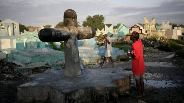 A voodoo believer prays at Baron Samdi cross in the cemetery of Croix des Bouquets on the outskirts of Port-au-Prince on 1 November, 2015