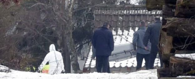 Police carry a coffin from the hut near Arnstein
