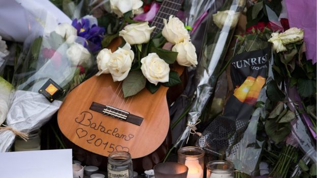 A guitar with white roses lies in front of the music venue Bataclan in Paris