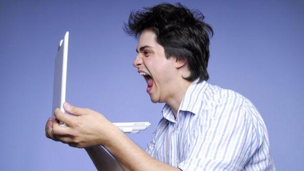 Hombre gritando a una computadora