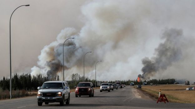 A convoy drives past wildfire in Canada
