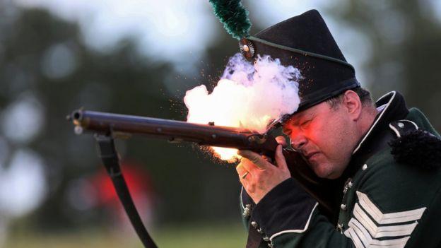 Un hombre con traje de época dispara un mosquete.