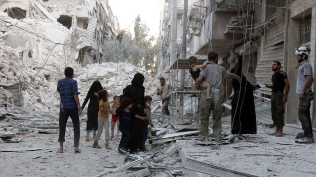 Family standing in rubble in Aleppo