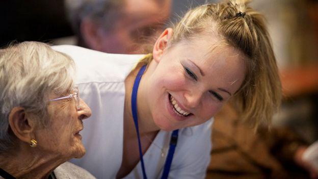 Una enfermera cuida de una anciana en un asilo.