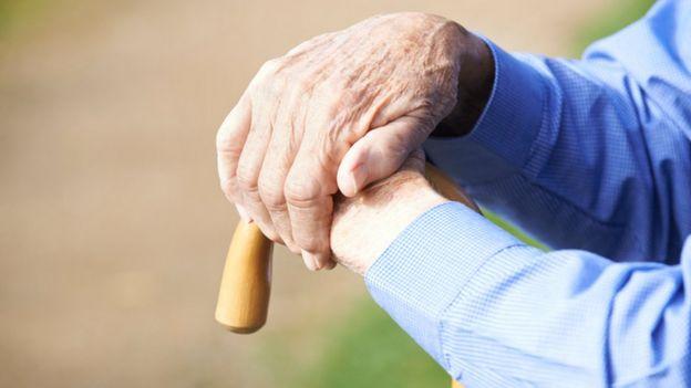 Manos de anciano apoyadas en una bastón.