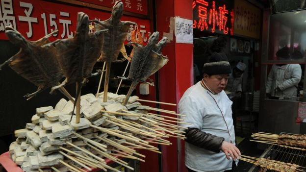 A street hawker cook lizards at his stall in the Wangfujing shopping street of Beijing on January 17 2012.