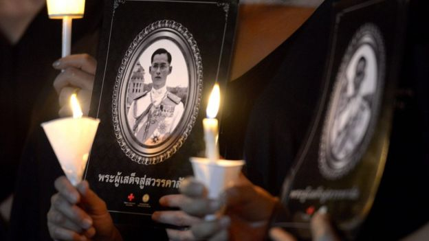 Thai people hold candles during a vigil in honour of late Thai King Bhumibol Adulyadej at a park in Bangkok on November 30, 2016