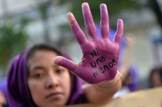 Mujer con la mano pintada en protesta por los feminicidios en México.