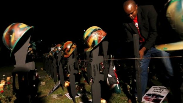 A volunteer arranges replicas of guns and helmets placed on the ground to symbolize Kenyan soldiers serving in the African Union Mission in Somalia (AMISOM) who were killed during an attack last week, at a memorial vigil within the