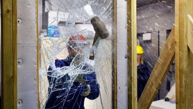 Un técnico rompiendo un vidrio con una mandarria