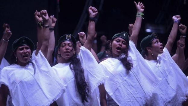 A choir of members of the Colombian Revolutionary Armed Forces of Colombia (FARC) guerrilla sing at the end of the broadcasting of the signing of the peace at El Diamante rebel camp, Caqueta department, Colombia on September 26, 2016