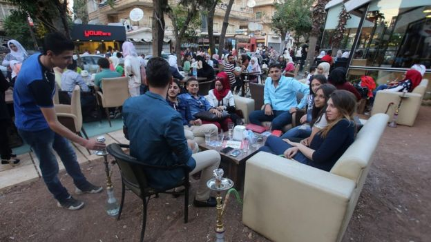 Syrian youths sits at a cafe in the government-held area of the northern Syrian city of Aleppo as they celebrate the Eid al-Adha Muslim holiday on September 13, 2016, a day after a fragile ceasefire was brokered. In the government-held western Aleppo, which is regularly targeted by rebel rocket fire, residents enjoyed the quiet of the morning and expressed hope that the truce would last.