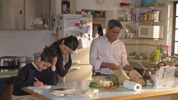 Familia prepara alimentos en una cocina