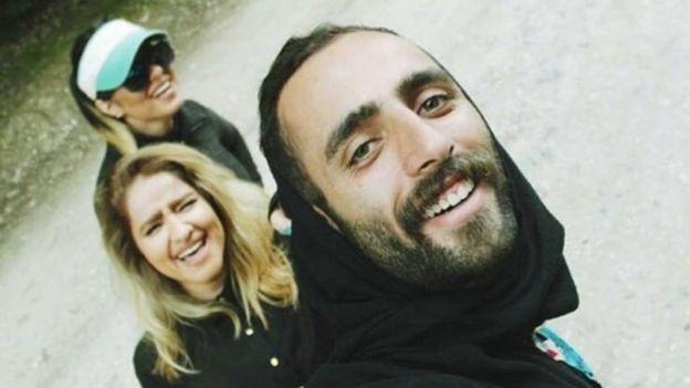 Un hombre con hyjab y dos mujeres sin él sonríen para la foto.