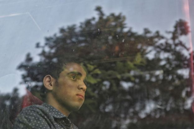 Young man stares out of bus window