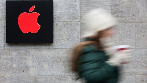 Una chica pasa una tienda de Apple con el logo en rojo por la campaña del World Aids Day (foto de diciembre).