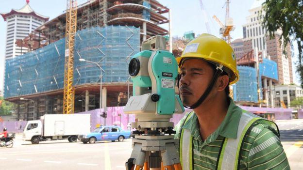 A migrant construction worker surveys a building site in Singapore