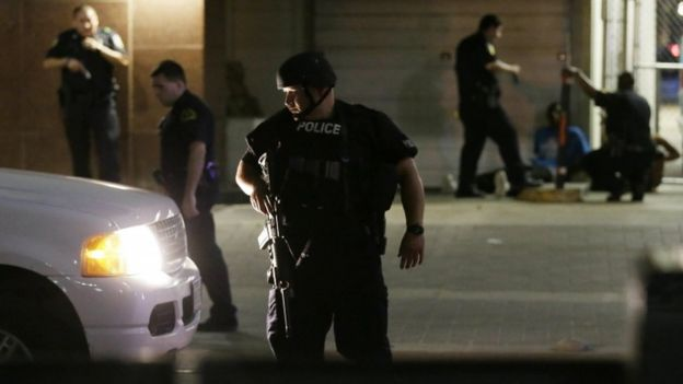 Dallas police detain a driver after sniper shootings
