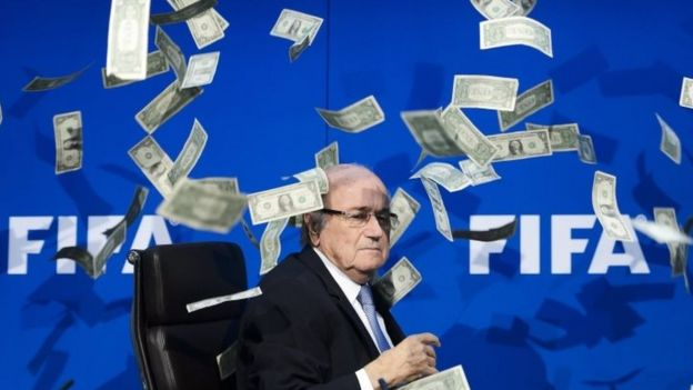 Fifa President Sepp Blatter at a press conference as fake dollar notes thrown by a British comedian fly around him (20 July 2015)