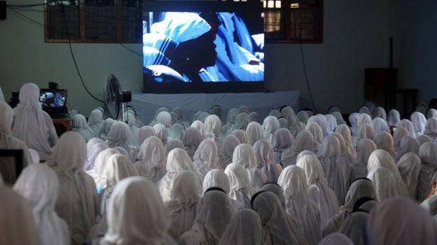 Freiras indianas da organização de Madre Teresa assistem a sua canonização pela TV
