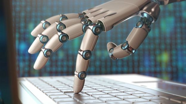 Robot escribiendo en computadora.