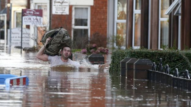 A man wades through flood water on a residential street in Carlisle