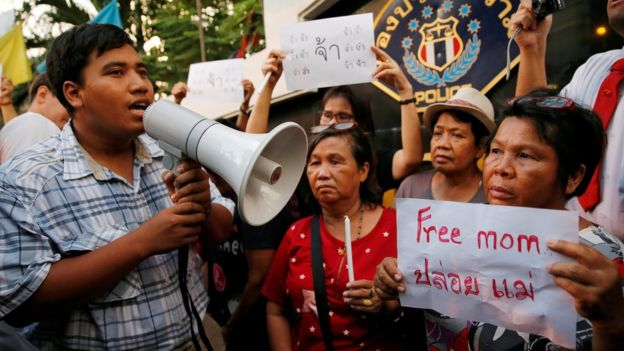 Anti-junta activist Sirawith Seritiwat, surrounded by supporters, holds a megaphone as part of a demonstration calling for the release of his mother