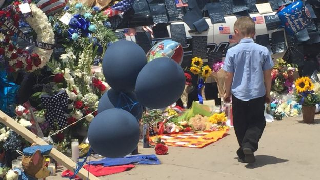 Boy looks at flowers in front of Dallas police HQ (10 July)
