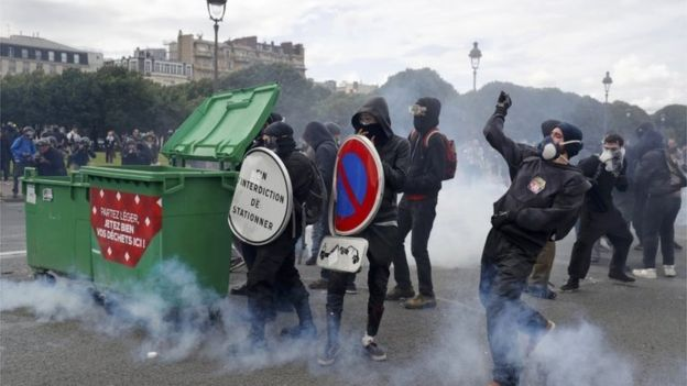 Masked youths face off with French police and gendarmes during clashes at the Invalides square during a demonstration in Paris as part of nationwide protests against plans to reform French labour laws.