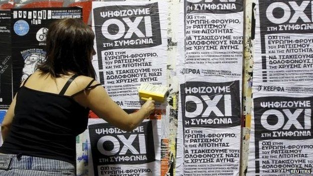 """A woman puts up referendum campaign posters with the word """"No"""" in Greek in Athens, Greece"""