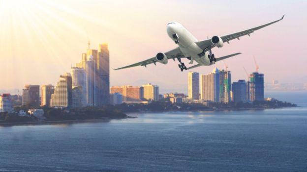 Un avión sobrevolando el mar. Al fondo una ciudad con rascacielos