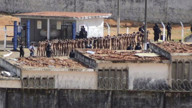 Naked inmates stand in line while surrounded by police after a riot at the Alcacuz prison in Nisia Floresta, Rio Grande do Norte state, Brazil,